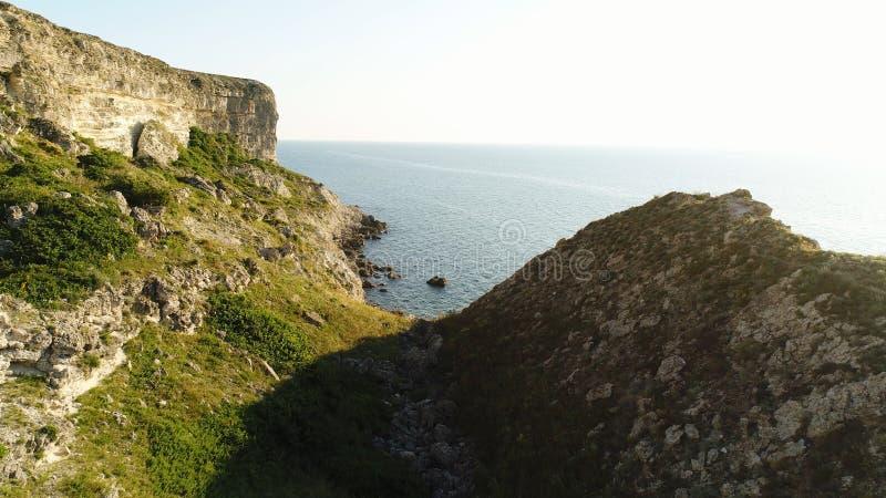 Mar azul pacífico e hierba verde fresca de una cuesta rocosa en el tiro de la costa Trayectoria mágica al mar sin fin con claro imagen de archivo libre de regalías