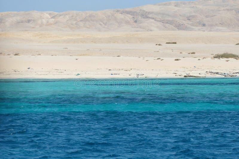Mar azul, praia branca, deserto e montanhas fotografia de stock