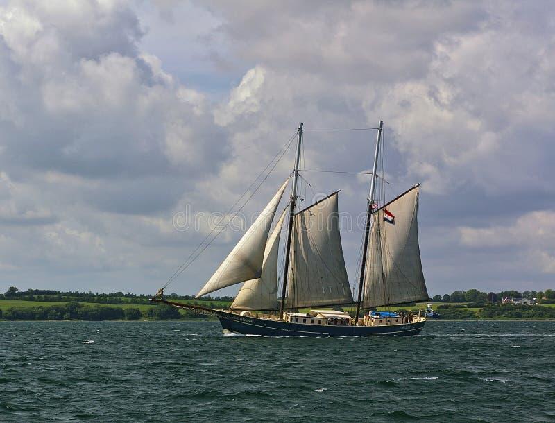 Mar Báltico, Dinamarca - 1 de julio de 2012 - velero holandés con la orilla verde en el fondo fotografía de archivo libre de regalías