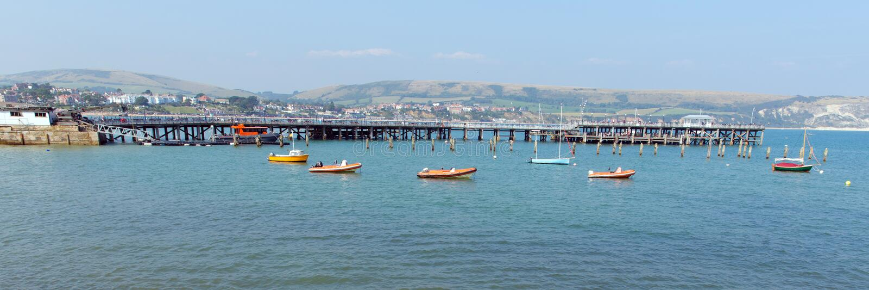 Mar BRITÂNICO do cais de Swanage Dorset Inglaterra e panorama da costa imagens de stock