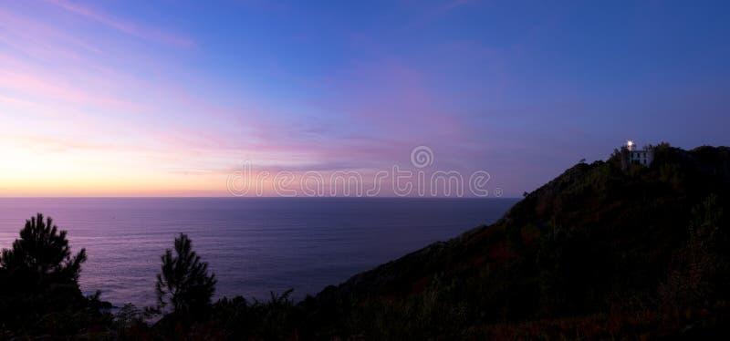 Mar cántabro y puesta del sol en el faro imagen de archivo