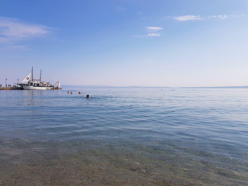 Mar calmo na manhã com o barco na natação do porto e dos povos imagens de stock royalty free