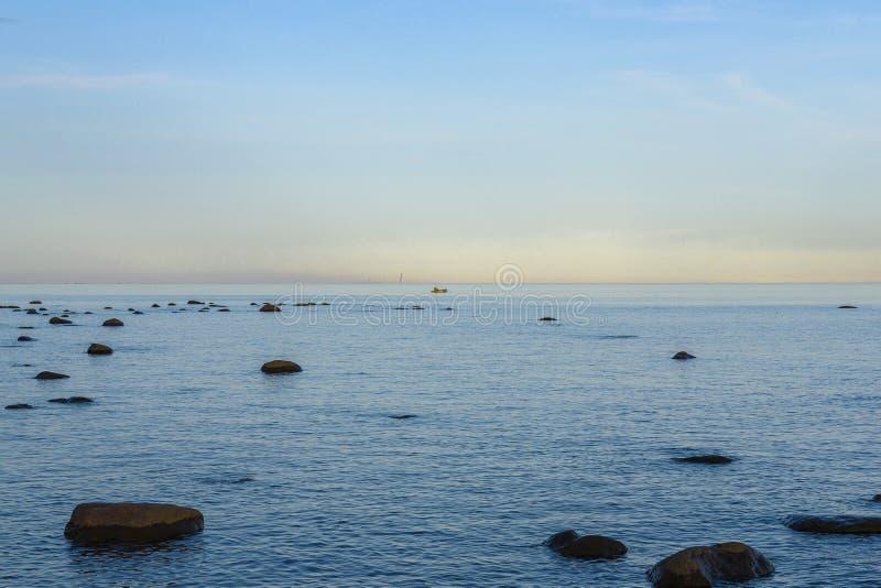 Mar com as pedras que colam fora dele pescador em um barco na praia distante e a silhueta da cidade face a um skyscrape imagens de stock royalty free