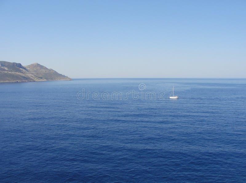 Mar con el barco de vela blanco solo fotografía de archivo
