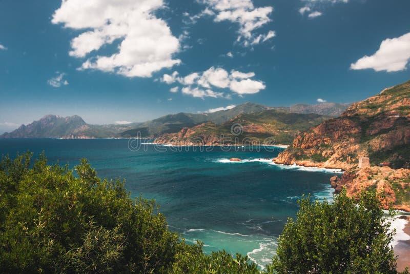 Mar, costa rocosa roja y una torre Genoese, Córcega, Francia imagenes de archivo