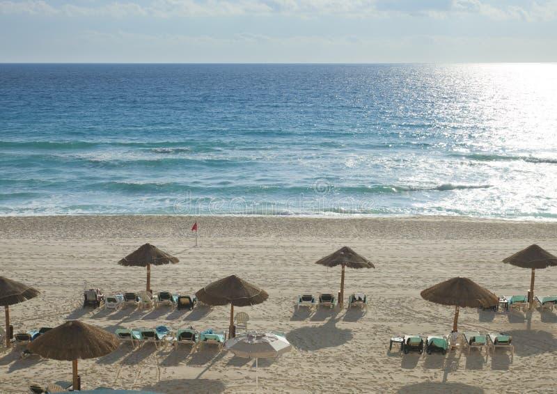 Mar das caraíbas e praia na manhã com cadeiras e abrigos fotografia de stock royalty free