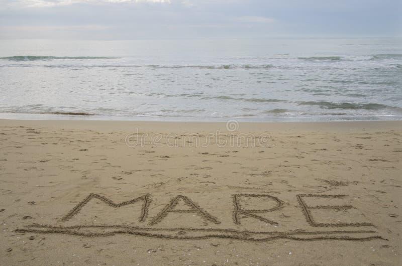 Mar de la 'yegua 'del mundo en la mano italiana escrita subrayada en la arena foto de archivo libre de regalías
