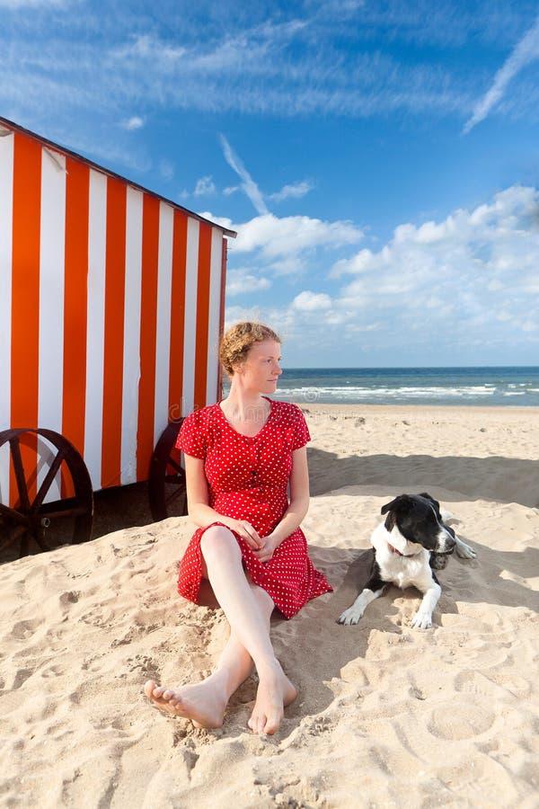 Mar de la cabina de la playa del perro de la mujer, De Panne, Bélgica imagen de archivo
