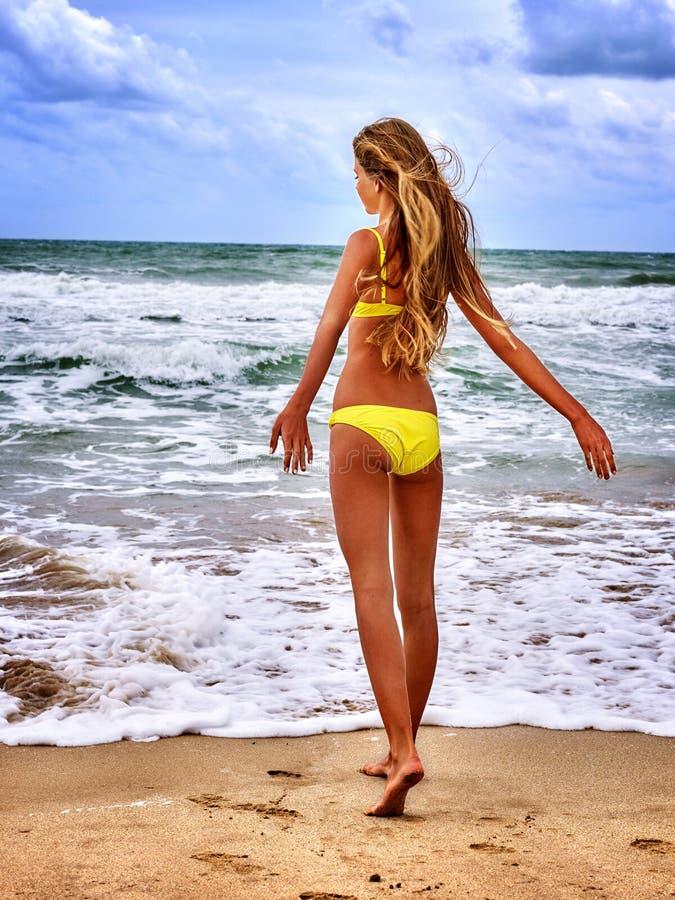 Mar de la muchacha del verano en traje de baño amarillo fotos de archivo libres de regalías