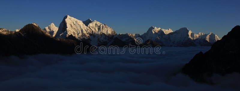 Mar de la niebla rodeado por las altas montañas fotografía de archivo