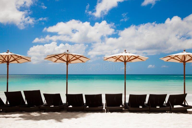 Mar de la turquesa, deckchairs, arena blanca y parasoles de playa imágenes de archivo libres de regalías