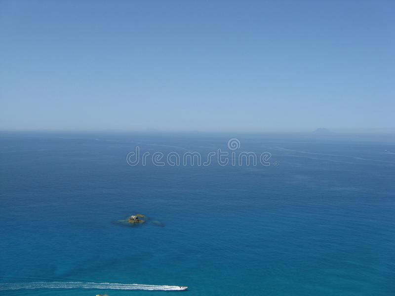 Mar de Skyblue com ilha rochosa e Stromboli fotos de stock