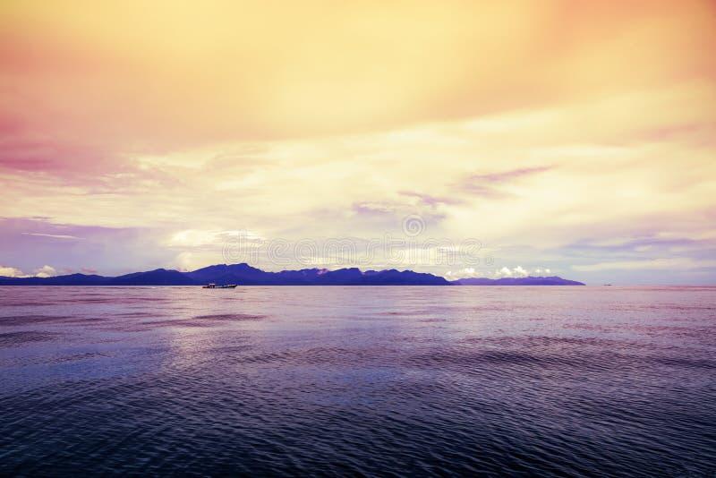 Mar debajo del cielo brillante durante la puesta del sol en la bahía de Pak Bara, Tailandia fotos de archivo