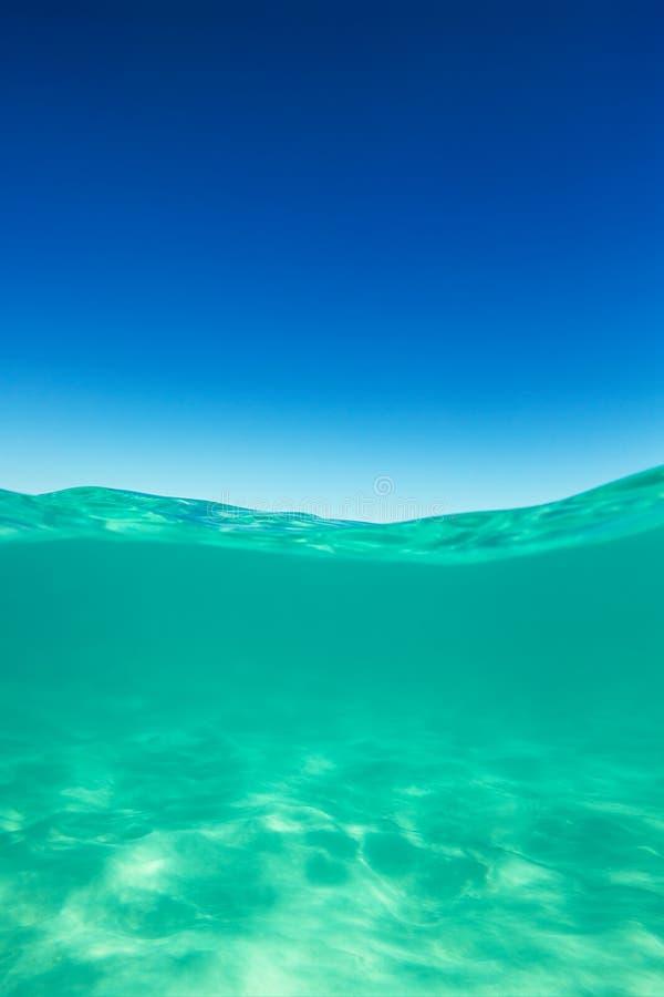 Mar del Caribe de la línea de flotación clara subacuático y encima con el cielo azul imágenes de archivo libres de regalías