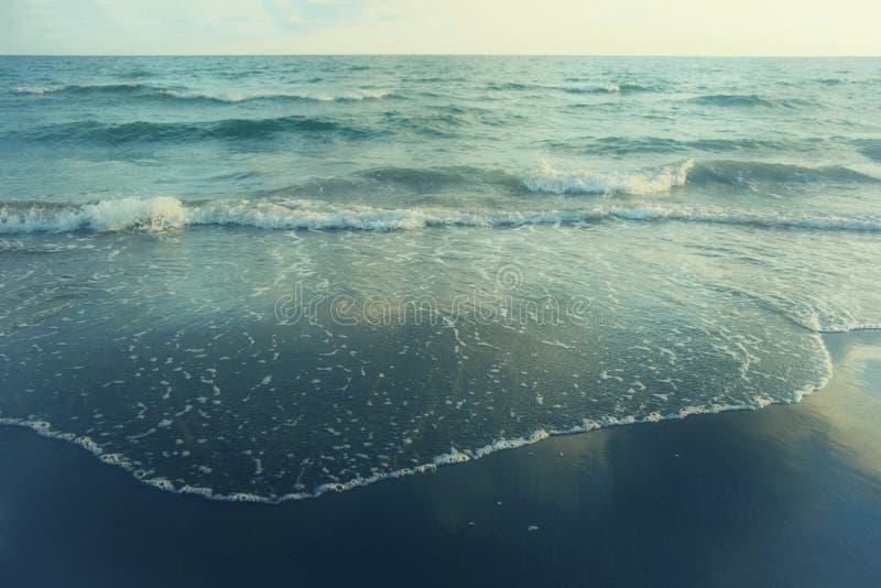 Mar del océano del fondo de la playa de la onda y vintage azul hermoso/de la película arenoso del tono fotos de archivo
