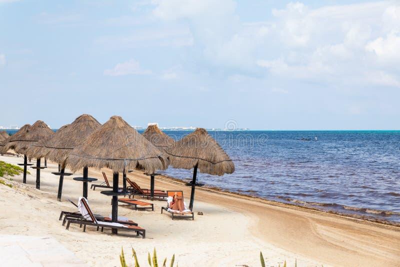 Mar do Caribe com cadeiras de praia e guarda-chuvas de grama em frente aos resorts do Palácio de Lua, Cancún, México imagem de stock royalty free