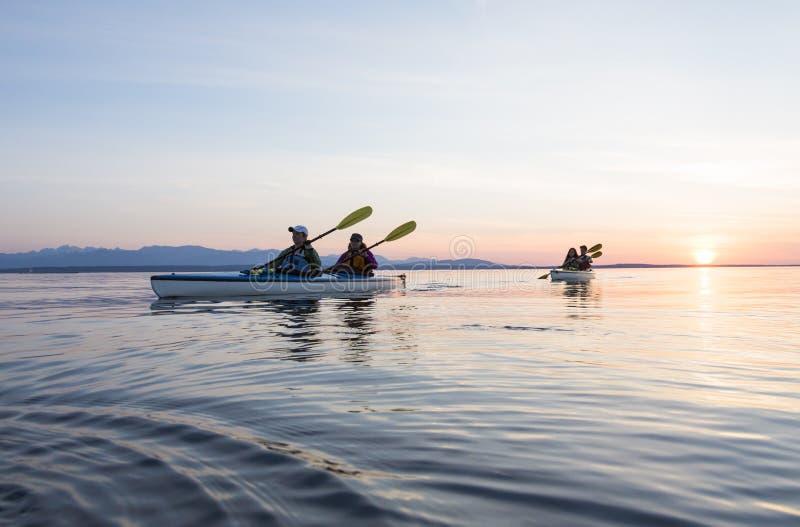 Mar dos amigos do grupo de pessoas que kayaking junto no por do sol na natureza bonita Esportes exteriores ativos da aventura foto de stock royalty free