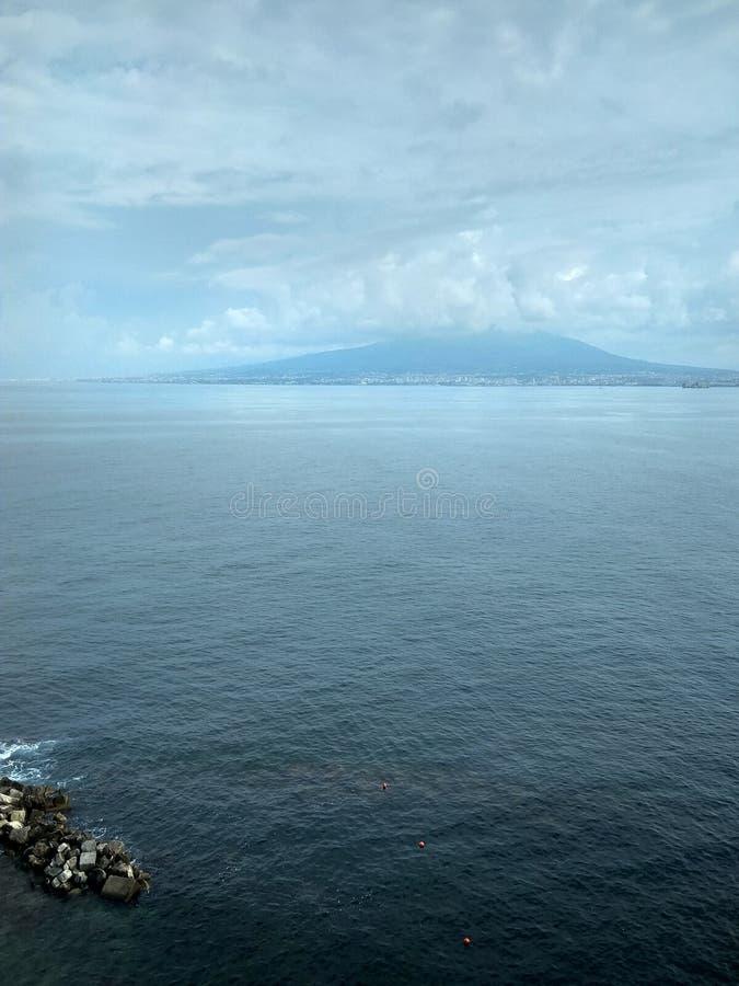 Mar e céu e costa azuis com pedras fotos de stock