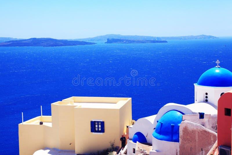 Mar e casas brancas com os telhados azuis de Santorini foto de stock royalty free