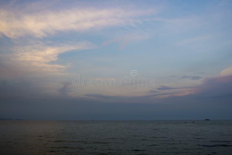 Mar e nuvens azuis no céu com reflexões da superfície e da luz solar da água foto de stock
