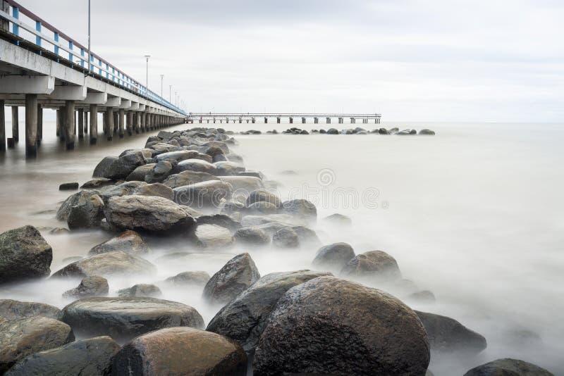 Mar, embarcadero y rocas fotos de archivo
