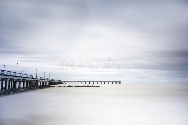 Mar, embarcadero y rocas fotografía de archivo