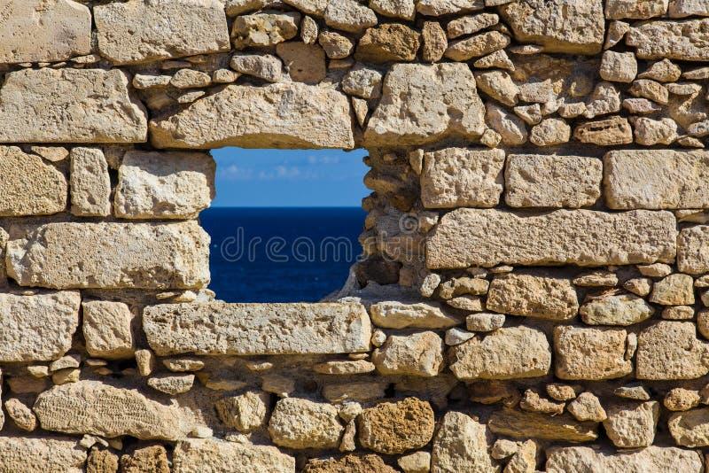 Mar en ventana vieja de la fortaleza de la pared de ladrillo foto de archivo libre de regalías