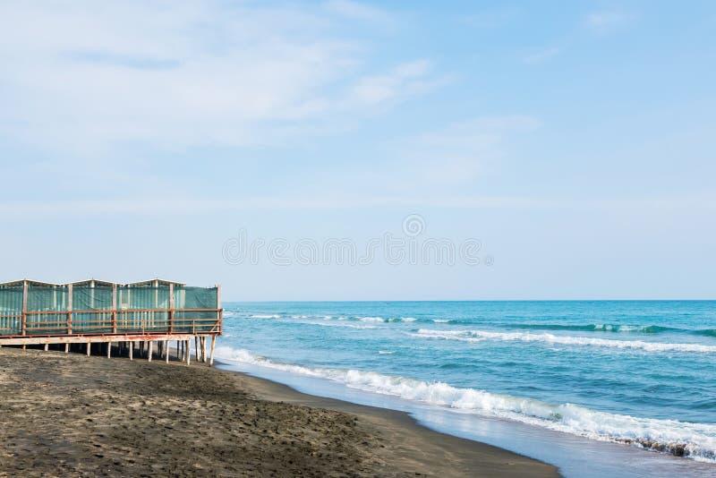 Mar hermoso, la playa arenosa negra y casas de playa rayadas blancas y azules imagenes de archivo