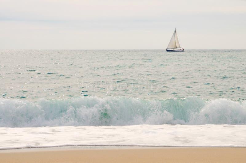 Mar, iate, céu com onda e praia no primeiro plano fotos de stock