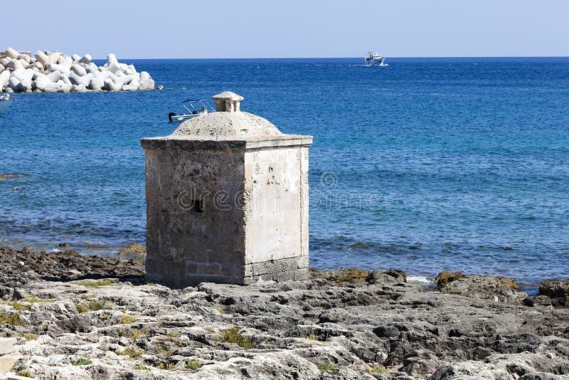 Mar Ionian Construção cúbica pequena nas rochas Mar azul fotos de stock