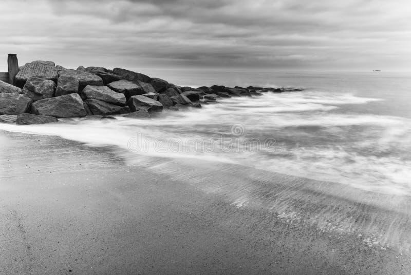 Mar lechoso que salpica sobre rocas foto de archivo
