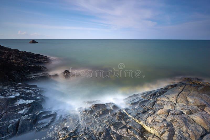 Mar liso a las rocas lechosas foto de archivo libre de regalías