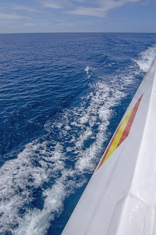 Mar Mediterráneo azul espumoso del barco de la bandera española blanca del lado fotografía de archivo libre de regalías