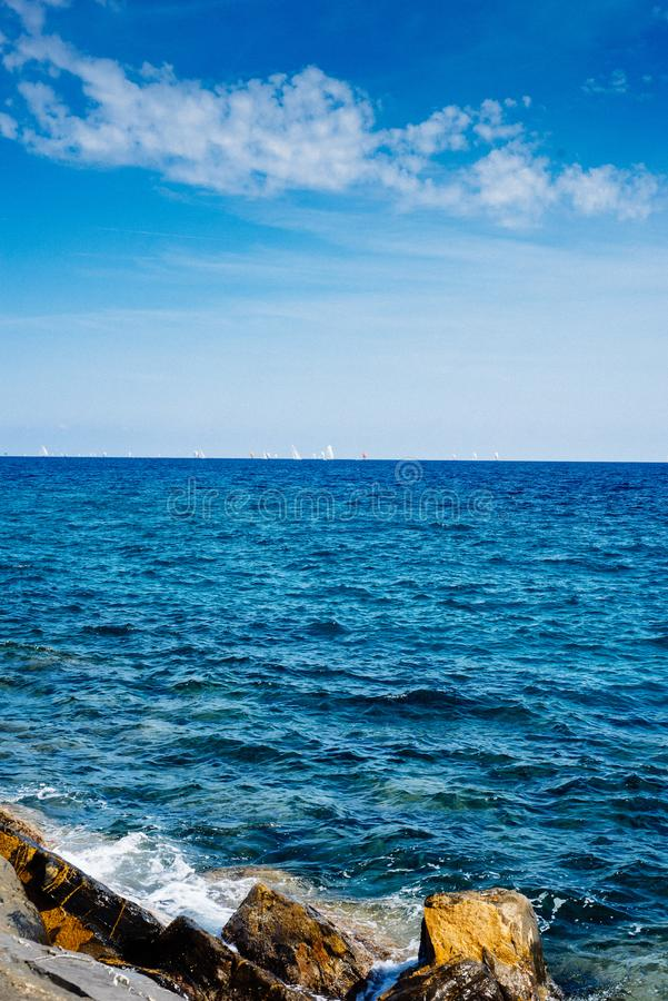 Mar Mediterráneo en Liguria, las rocas y los veleros en el distanc fotografía de archivo