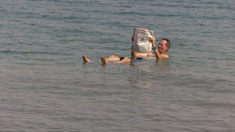 MAR MUERTO, ISRAEL - SEPTIEMBRE, 22, 2016: un hombre flota en el mar muerto y lee un periódico imágenes de archivo libres de regalías