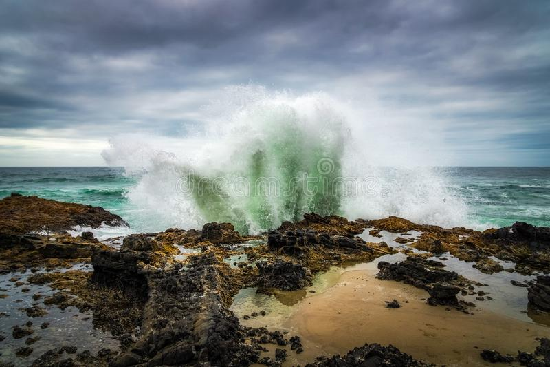 Mar o ola oceánica que se estrella en un promontorio o una orilla basáltico o rocoso foto de archivo