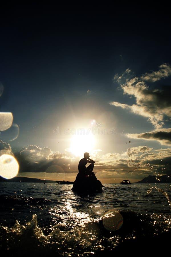 Mar, piedra, pensando alrededor.? foto de archivo
