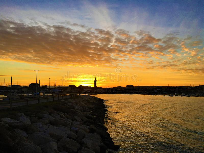 Mar, por do sol, água, céu e nuvens em Civitanova Marche, Itália imagens de stock royalty free