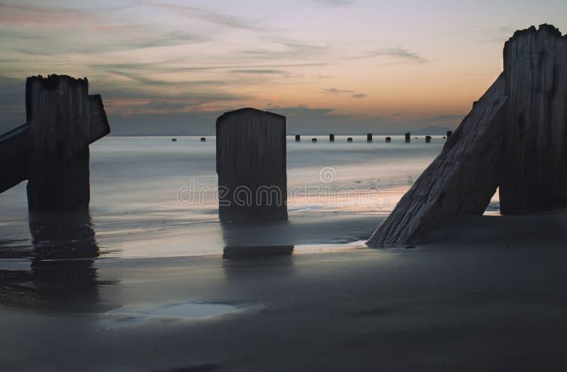 Mar, postes y puesta del sol fotografía de archivo