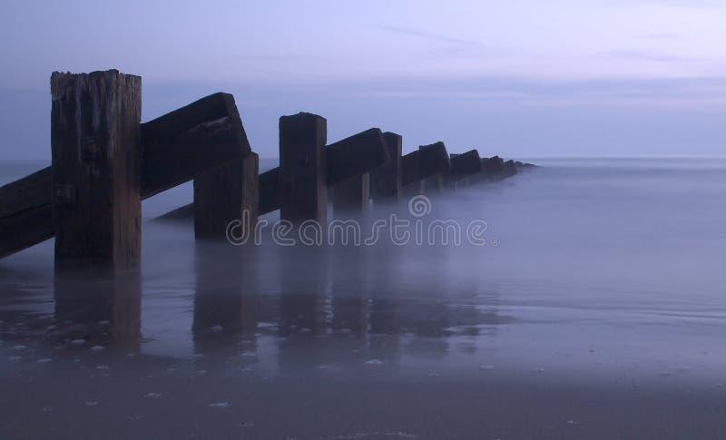 Mar, postes y puesta del sol imagenes de archivo