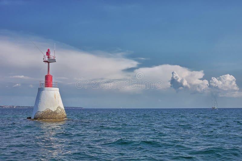 Mar precioso con el pequeño faro rojo y un velero imagenes de archivo