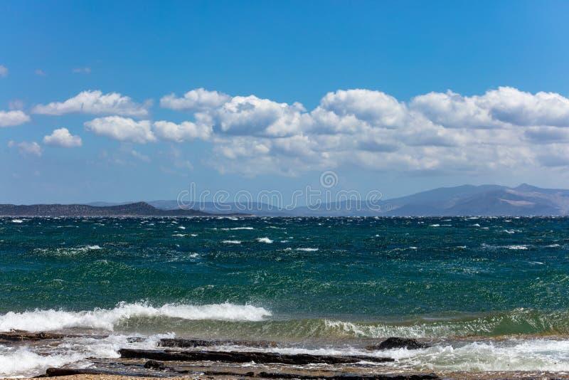 Mar tormentoso, ondas que espirram nas rochas, céu azul com fundo das nuvens foto de stock royalty free