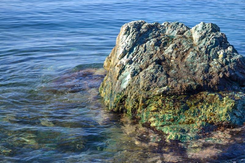 Mar tranquilo de la costa de mar A sin las ondas Un canto rodado grande Aguas transparentes del mar adriático imagenes de archivo