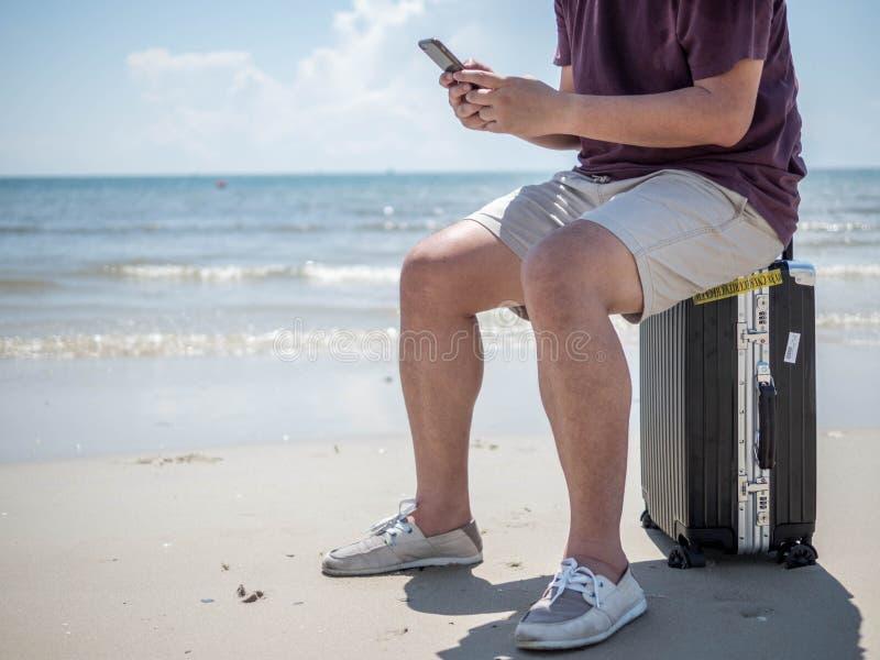 Mar tropical, assento do homem novo no saco de viagem e utilização do telefone esperto na praia Projeto de conceito de viagem das imagens de stock royalty free