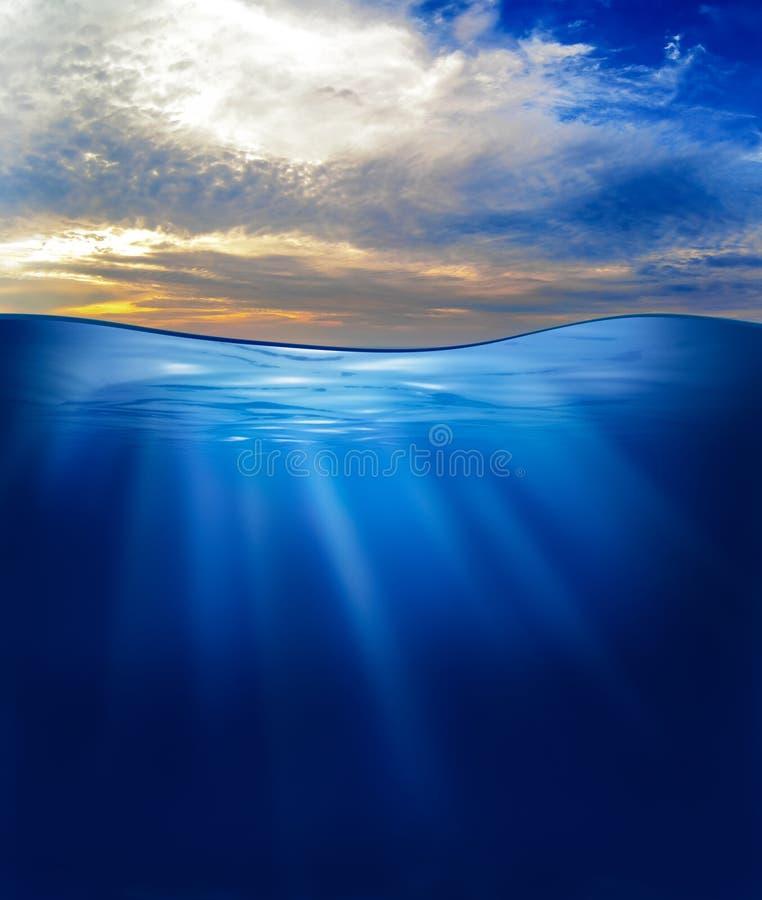 Mar u océano subacuático con el cielo de la puesta del sol foto de archivo libre de regalías
