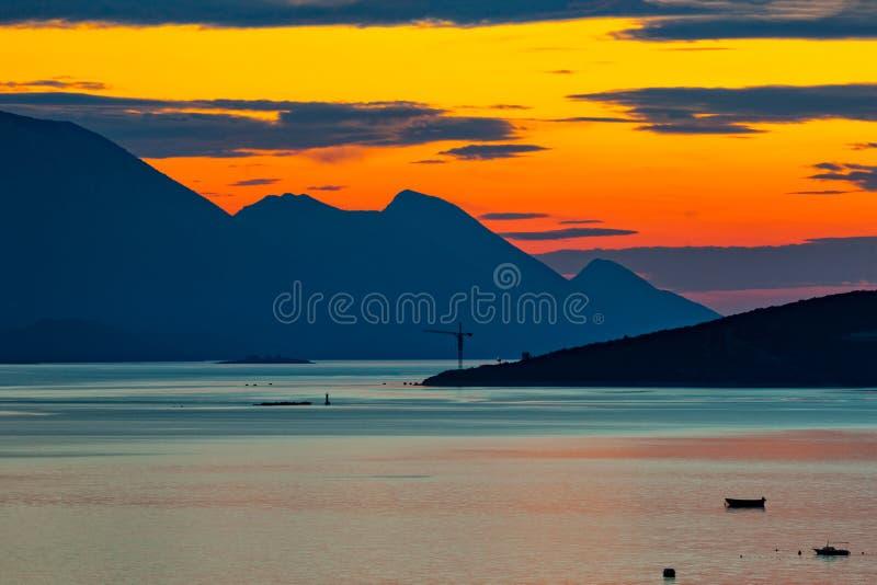 Mar y montañas en la puesta del sol - silueta fotos de archivo libres de regalías