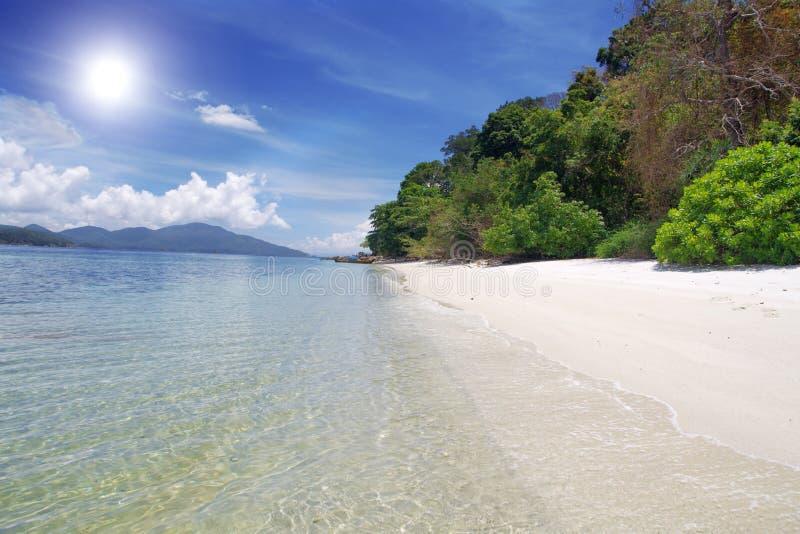 Mar y playa con la arena blanca foto de archivo