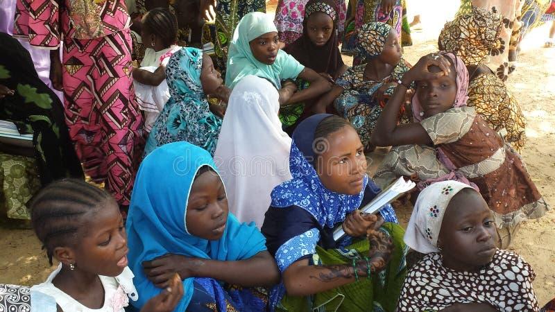 Maradi Niger: Muslimska skolaflickor som får skydd från den extrema värmen i Niger under en skugga av ett träd, förutom deras sc royaltyfri bild