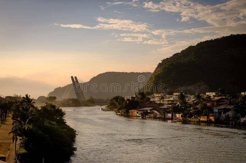 Marapendi Lagoon seen from above with houses on the hill during sunset, golden light. Jet skis are riding on the lake. Barra da Ti. Juca, Rio de Janeiro stock image