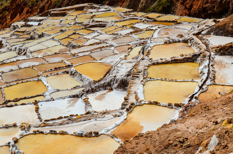 MARAS, CUSCO REGION, PERU- JUNE 6, 2013: Salt mines of Maras- Thousands of uneven square-shaped ponds dot the hillside slopes. Maras is well known for its nearby royalty free stock photography